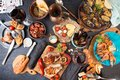 Overhead of dinner table. Assorted delicious grilled barbecue me Royalty Free Stock Photo