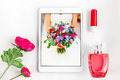 Overhead of essentials on white background laptop pomade flower perfume pad tablet outfits or set modern young girl student woman Stock Photos
