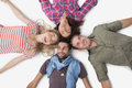 Overhead of friends lying in a circle on white background Stock Photo