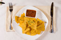 Overhead of nacho chips and salsa on plate at place setting table Stock Photography