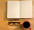 Overhead of open notebook with pen glasses and coffee on a desk Stock Photography