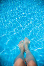 Overhead photo of feet on a background of water in swimming pool. Women feets view from above. Swimming pool, relax, health Royalty Free Stock Photo