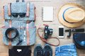 Overhead shot of essentials for traveler. Outfit of young man traveler, camera, mobile device, sunglasses. Royalty Free Stock Photo