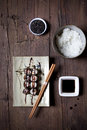 Overhead shot of hosomaki sushi on plate with soy sauce and ingredients on table Royalty Free Stock Photo