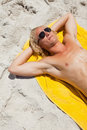 Overhead view of a blonde man lying on his beach towel Royalty Free Stock Photos