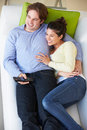 Overhead view of couple watching tv on sofa together smiling Royalty Free Stock Photos