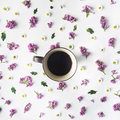 Overhead view of cup of black coffee and bouquet of chamomile and lilac Royalty Free Stock Photo