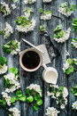 Overhead view of cup of black coffee, milk, pen, glasses and white flowers and branches  on white background Royalty Free Stock Photo
