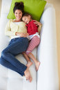 Overhead view of mother and daughter relaxing on sofa smiling to camera Stock Photography