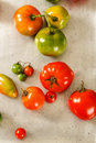 Overhead view of red and green homegrown tomatoes mixed varieties rest on an old worn vintage metal baking sheet Stock Photography
