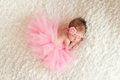 An overhead view of a sleeping newborn baby girl wearing a pink crocheted headband and tutu she is sleeping on white billowy Royalty Free Stock Image