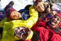 Overhead View Of Teenage Family Lying In Snow Stock Photo