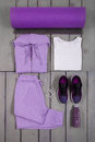 Overhead view woman's workout outfit. Female sports equipment. Purple sport pant, shoes, suit, mat, water bottle white Royalty Free Stock Photo