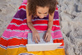 Overhead view of a young woman using her laptop on her beach towel Royalty Free Stock Photos