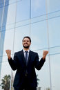 Overjoyed businessman raising his arms in victory outside a office building an excited man with winner spirit celebrating success Royalty Free Stock Photography
