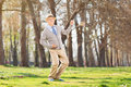 Overjoyed senior playing air guitar outdoors in park Royalty Free Stock Photography
