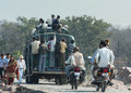 Overloaded public transport bus orchha india circa february carrying people on top and hanging out at the back Stock Photo