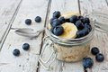 Overnight oats with blueberries and bananas on a white wood background Royalty Free Stock Photo
