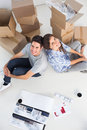 Overview of a couple sitting back to back in their new house Royalty Free Stock Photography