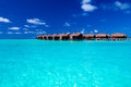 Overwater villas in blue tropical lagoon of shallow water Royalty Free Stock Photography