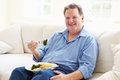 Overweight Man Eating Healthy Meal Sitting On Sofa Royalty Free Stock Photo