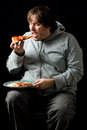 Overweight man eating a pizza. Royalty Free Stock Photos