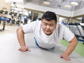 Overweight man exercising an young doing push ups with sweating face Stock Photo