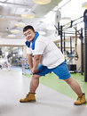 Overweight man exercising young at fitness center Royalty Free Stock Photography