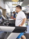 Overweight man exercising an young running on treadmill in fitness center Stock Image