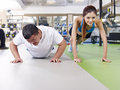Overweight man and slim girl exercising together an young men doing push ups with a young lady Stock Photos