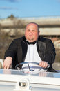 Overweight man in a tuxedo at the helm of a pleasure boat closeup Royalty Free Stock Photography