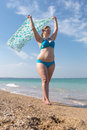 Overweight middle-aged woman with pareo walks along seashore Royalty Free Stock Photo
