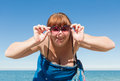 Overweight middle aged woman at the sea looking camera through tinted sunglasses smiling Stock Photo