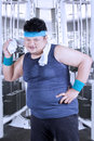 Overweight person cleaning sweat at gym portrait of fat with sportswear using a towel to clean his after workout in fitness center Stock Photos