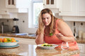 Overweight Woman Eating Healthy Meal In Kitchen Royalty Free Stock Photo