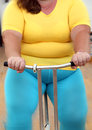 Overweight woman exercising on bike simulator body of Royalty Free Stock Photo