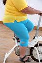 Overweight woman exercising on bike simulator body of Stock Photos