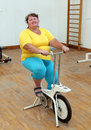 Overweight woman exercising on bike simulator smiling Stock Photo