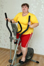 Overweight woman exercising on trainer Stock Image