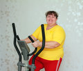 Overweight woman exercising on trainer Royalty Free Stock Image