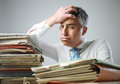 Overwork stressed businessman with a too much paperwork and files piled up on the table Royalty Free Stock Images