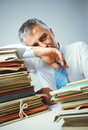 Overwork stressed businessman with a too much paperwork and files piled up on the table Royalty Free Stock Photo