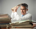Overwork stressed businessman with a too much paperwork and files piled up on the table Royalty Free Stock Photography