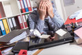 Overworked businessman sitting at a messy desk Royalty Free Stock Photo