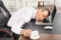 Overworked man sleep on laptop at office with cup Stock Image