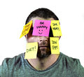 Overworked man in stress with face full of post it notes covering him with reminders and resolutions young overwhelmed stuck Royalty Free Stock Photography