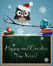 Owl happy and creative new year little brown on snowy branch with chalkboard globe books text Stock Photography