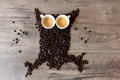 Owl shaped figure made out of coffee beans and two full espresso cups on top of a table Royalty Free Stock Photo