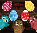 Owls keep Easter decorated eggs on a stick. Multicolored. Vector