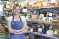 Owner of delicatessen standing next to cheese display portrait Royalty Free Stock Photo